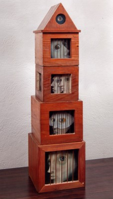 """Los Encarcelados"" (The Imprisoned) 1965, 4 stacked wood cages with bars and painted Masonite heads inside each, 42 ⅛ x 9 ⅞ x 10 ⅝ inches (107 x 25 x 27 cm). Collection of Carlos de Laborde"
