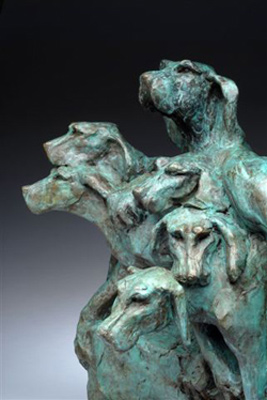 """""""Kennel Up"""" (detail) Bronze, 15 x 12.5 x 16 inches, Signed. Here a pack of fox hounds has been asked to """"kennel up"""" which means get back into the kennel (or truck or onto a bench). Hounds have such beautiful heads and athletic bodies. The three hounds on the front and sides hold back the entire pack from falling off the base. The only thing I couldn't provide was the magic of their voices."""