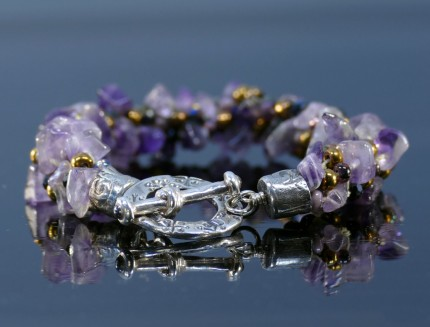 """Amethyst Dream Bracelet"" Overall Length 8.75"", Price: $329, Chisholm Ref. #: SB-108 - One of a kind beaded bracelet woven with amethyst, glass, and Czech crystal beads. The end caps have a swirling texture, the toggle clasp bears the warmblood breed logos, and the closure is set with two garnets cabuchons. Findings are hancrafted in .960 silver."