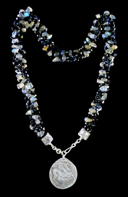 """Pegasus Blue Glow Silver & Beadwork Necklace"" Pendant: 1.25"" diameter, Overall length: 21"", Price: $650, Chisholm Ref. #:SBW-N7 - This one-of-a-kind silver & beadwork necklace is made of labradorite, jet, and Czech fire polished crystals. The handmade silver end-caps are deeply textured. The focal piece of the necklace is a large, Pegasus pendant modeled on a Greek coin. The reverse of the pendant is impressed with the pattern of a real feather. Handcrafted in .960 silver."