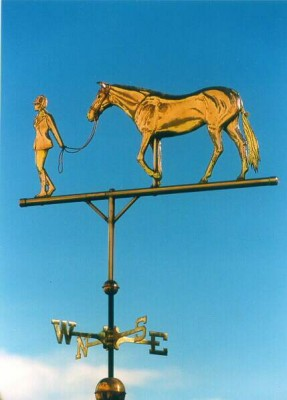 """Dutch Warm Blood Horse with Young Woman Rider Weathervane"" The Warmblood horse weathervane  was made using copper and brass (no gold leaf) so as the weathervane weathers the contrast between the reddish copper tones and the yellower brass tones will become more subtle, as opposed to the image on the right where the gold leaf yellow tones will stay a shiny golden color.  The original version of this design was commissioned by a husband for his wife.  Their daughter who is an excellent equestrian has just left for college and the mother missed her greatly.  Now when she looks out her window towards the barn, it brings her daughter to mind and puts a smile on her face. An interesting thing about this particular design is that it is composed of 2 distinct elements, the horse and the girl.  Normally in a 3-foot horse weathervane the horse would be 3 feet in size, however in this 3-foot weathervane, the horse is closer to 2 feet in size.  In the case where a weathervane has more than one subject you may sometimes need to go a larger size than you would if the weathervane consisted of only one design element."