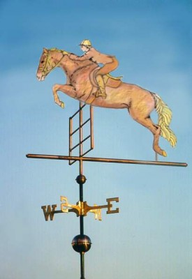 """Jumping Horse with Rider Weathervane"" Per our customer's request, the Jumping Horse and Rider weathervane featured in this photo was made in all copper with no gold leaf or brass accents. Because our vanes are made to order, we can make each weathervane according to our customer's preferences. The all copper weather vane is very traditional. The use of brass in the sculpture piece complements the brass directionals (north, south, east and west arms). Gold leaf accents create a bolder, more distinctive contrast between all the various elements that comprise the weathervane.  The Jumping Horse weathervane with Rider featured here was made in the extra-large size (four feet from tip of nose to end of tail) for a large indoor riding area on the east coast. It was done in a combination of copper and brass although we often add gold leafed accents (mane, tail, rider's face, hands, boots or saddle blanket, etc). Our Jumping Horse weathervane  (shown to the right) features a vane where the gold leafing was added."