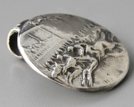 """Ahead By A Nose"" 1"" diameter, Price: $189, Chisholm Ref. #: S-SH2 - This silver piece captures the excitement of a close horse race. Horses and jockeys vie for position in the foreground. Behind them spectators crowd the rail with the grandstand rising in the background. Handcrafted in .960 silver."